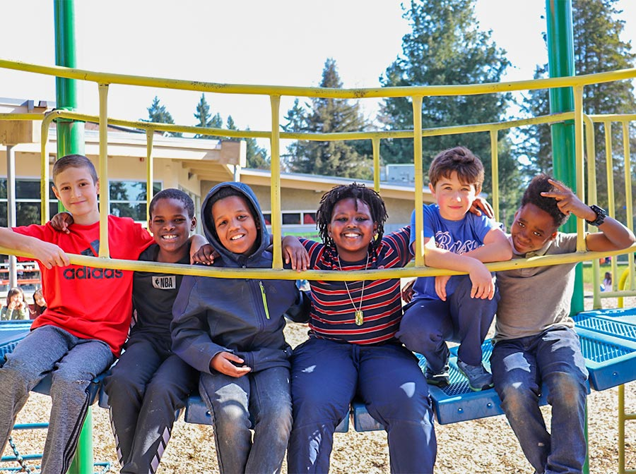 Six children posing for a photo on playground equipment